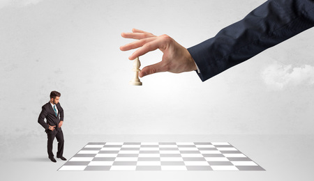 Little businessman playing chess with a big hand concept 版權商用圖片