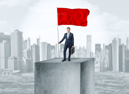 Businessman on the top of the city holding flag