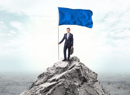 Businessman on the top of a the mountain holding flag