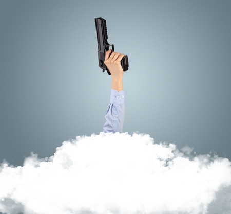Hand hold a gun buried into cloud