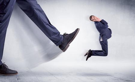 Big leg kicking small man Banco de Imagens