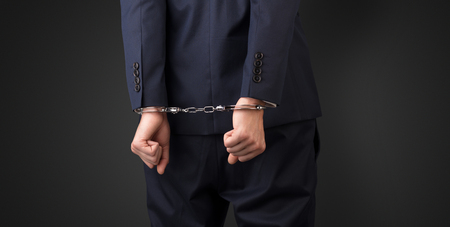 Dark backgrounded close handcuffed man Stock Photo
