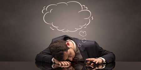 Businessman sleeping and dreaming at his workplace Foto de archivo