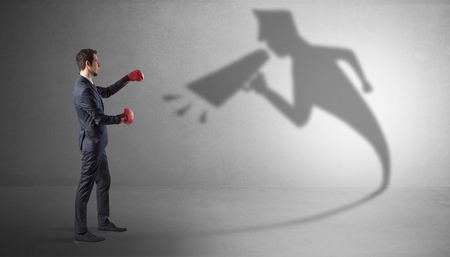 Businessman fighting with his bossy shadow Stock Photo