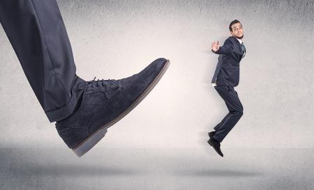 Small businessman kicked by big shoe Stock Photo