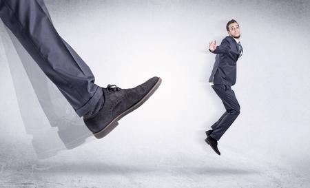 Black shoe kicking small man