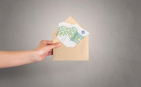Hand holding envelope with empty wall background Reklamní fotografie