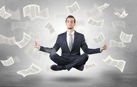 Businessman meditating with flying paper concept 写真素材
