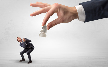 Big hand with chessman down small weak businessman concept