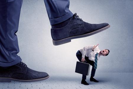 Young businessman getting crushed Stock Photo
