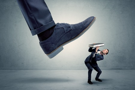 Employee getting trampled by big shoe Stock Photo