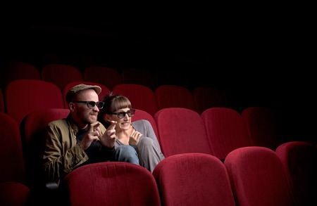 Young couple sitting at red movie theatre Stockfoto