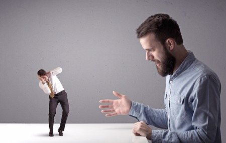 Young businessman fighting with miniature businessman