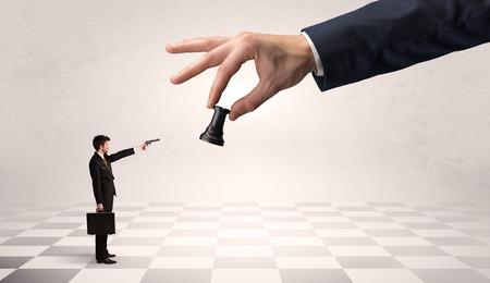 Businessman fighting against big chessman on a big hand Фото со стока - 111141069
