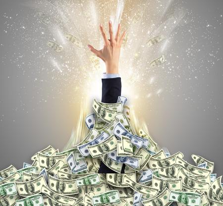 Hand bursting from a money heap