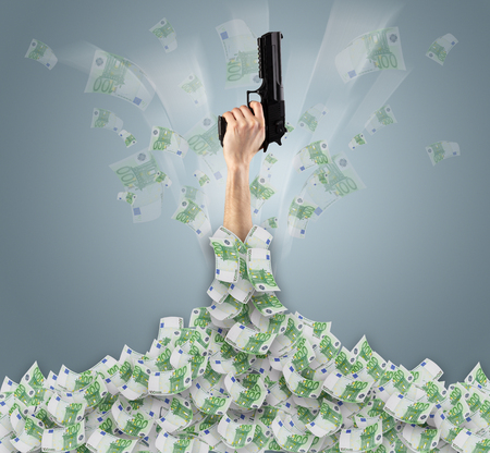 Hand buried in cash pile and trying to get out Stock Photo