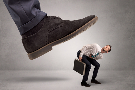 Small man trampled by the great power Stock Photo