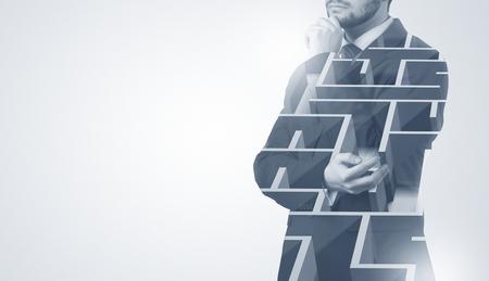 Geschäftsmann, der mit Labyrinth steht und denkt Standard-Bild
