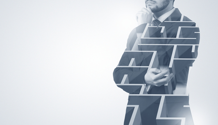 Uomo d'affari in piedi e pensando con labirinto Archivio Fotografico