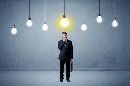 Businessman standing uninspired with bulbs above 스톡 콘텐츠