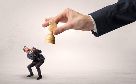 Big hand with chessman down small weak businessman concept Фото со стока - 111190659