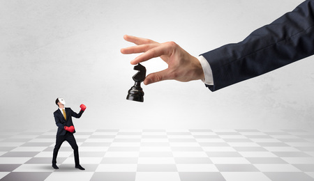Businessman fighting against big chessman on a big hand Фото со стока - 111190704