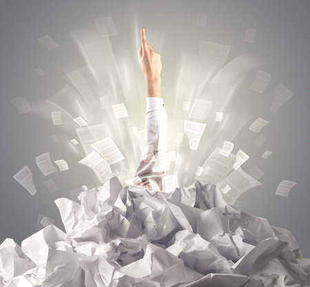 Hand coming out from paper pile Stock Photo - 111557213