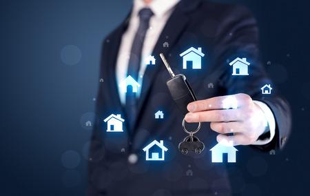 Businessman holding keys with houses around Stockfoto
