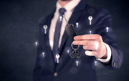 Businessman holding keys with keys around