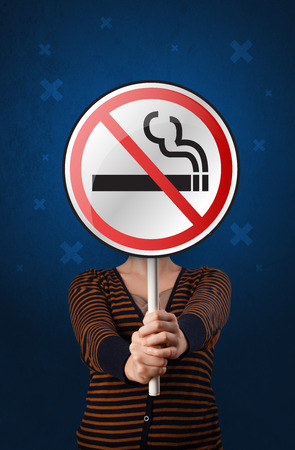 Woman holding no smoking sign