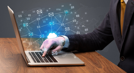 Hand sending a bunch of messages on laptop concept