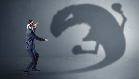 Businessman fighting with a big monster shadow