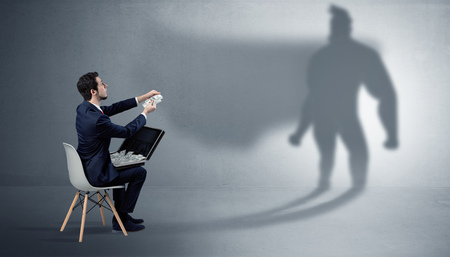 Businessman staying and offering stuffs to a superhero shadow Imagens
