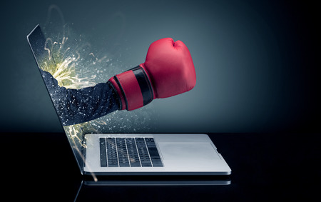 Hand with box gloves coming out of a laptop Standard-Bild