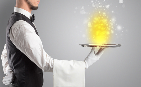 Waiter serving mysterious light on tray