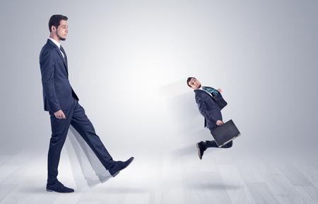 Giant businessman kicking out little businessman