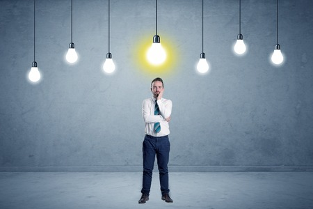 Businessman standing uninspired with bulbs above Stock Photo