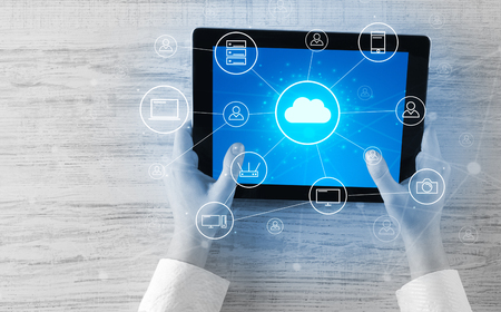 Mano usando tableta con concepto de sistema de computación en la nube centralizado Foto de archivo
