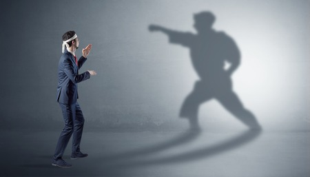 Young businessman fighting with his shadow