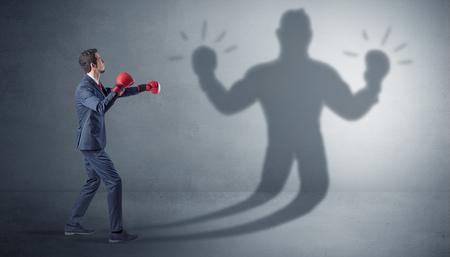 Businessman fighting with his unarmed shadow Фото со стока