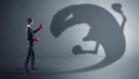 Uomo d'affari in lotta con una grande ombra mostro
