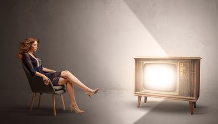 Young lady watching to a vintage television