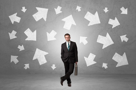 Businessman standing with arrows around Stock Photo