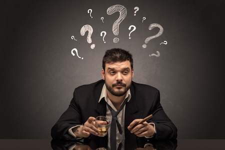 Drunk disappointed man with question signs concept Standard-Bild