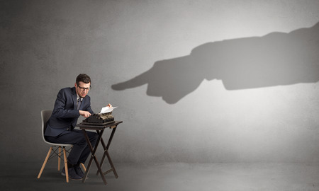 Shadow hands pointing at a small worker Banco de Imagens
