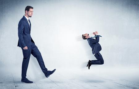 Big businessman kicking small businessman