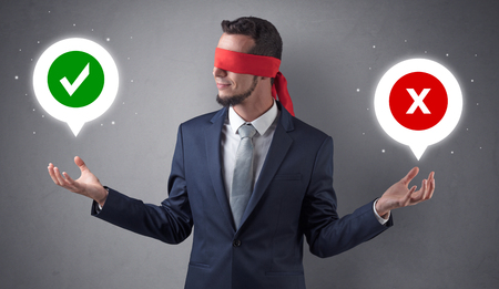 Blindfolded businessman trying to choose 免版税图像