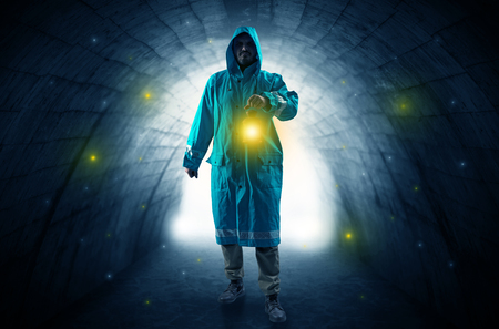 Man walking with lantern in a dark tunnel