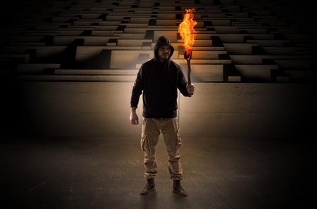Homme venant avec flambeau brûlant du concept de labyrinthe Banque d'images