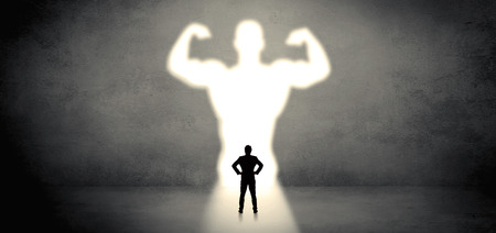 Businessman standing in front of a strong hero vision Фото со стока